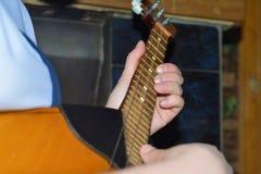 Το κορίτσι παίζει το dombra και κτυπά τις χορδές στην κιθάρα, κινηματογράφηση σε πρώτο πλάνο στοκ εικόνες