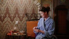 Το κορίτσι παίρνει έναν κύλινδρο με μια πρόβλεψη ενός φλυτζανιού του τσαγιού απόθεμα βίντεο