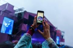 Το κορίτσι παίρνει ένα φεστιβάλ μουσικής, μια συναυλία στο smartphone στοκ εικόνα
