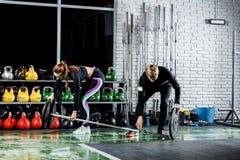 Το κορίτσι παίρνει έτοιμο για την άσκηση με τον εκπαιδευτή Στοκ Φωτογραφία