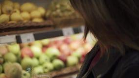 Το κορίτσι παίρνει το μαρούλι και την ντομάτα από ένα ράφι σε μια υπεραγορά απόθεμα βίντεο