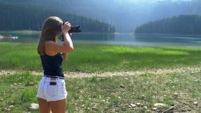 Το κορίτσι παίρνει μια εικόνα στέκεται στα πλαίσια του τοπίου φιλμ μικρού μήκους