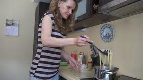 Το κορίτσι παίρνει τα έτοιμα μακαρόνια από το δοχείο στο πιάτο γυαλιού 4K απόθεμα βίντεο