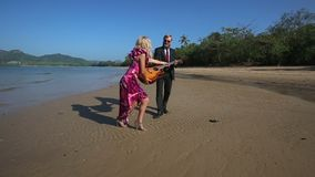 Το κορίτσι παίρνει την κιθάρα από τον κιθαρίστα παρουσιάζει νίκη στην παραλία φιλμ μικρού μήκους