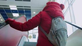 Το κορίτσι παίρνει την κυλιόμενη σκάλα απόθεμα βίντεο