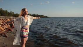 Το κορίτσι παίρνει τη βαθιά εισπνοή απολαμβάνοντας το καθαρό αέρα στην παραλία απόθεμα βίντεο
