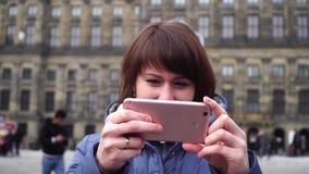 Το κορίτσι παίρνει τις εικόνες σε ένα smartphone στο τετράγωνο φραγμάτων φυλακτών φιλμ μικρού μήκους