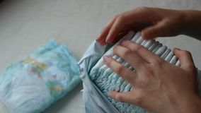 Το κορίτσι παίρνει τις πάνες μωρών από τη συσκευασία, κινηματογράφηση σε πρώτο πλάνο φιλμ μικρού μήκους