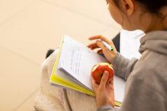Το κορίτσι παίρνει τις σημειώσεις και ένα μήλο στοκ φωτογραφία με δικαίωμα ελεύθερης χρήσης