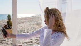 Το κορίτσι παίρνει τις φωτογραφίες στο κινητό τηλέφωνο, παραλία το καλοκαίρι, selfie στη μνήμη, διακοπές στα τροπικά νησιά, προκλ απόθεμα βίντεο