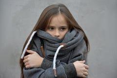 Το κορίτσι παγώματος αγκαλιάζει στοργικά στο μάλλινο πουλόβερ της Στοκ Φωτογραφία