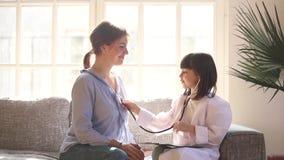 Το κορίτσι παιδιών έντυσε σε ομοιόμορφο ως παιχνίδι γιατρών με το mom φιλμ μικρού μήκους