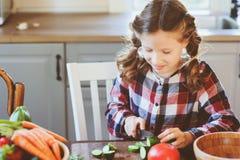 Το κορίτσι παιδιών βοηθά mom να μαγειρεψει και να κόψει τα φρέσκα λαχανικά για τη σαλάτα με το μαχαίρι Στοκ Εικόνες