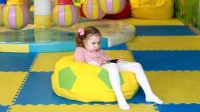 Το κορίτσι παιδιών εξετάζει το κινητό τηλέφωνο Το μωρό παίζει στο smartpho φιλμ μικρού μήκους