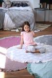 Το κορίτσι παιδιών κάθεται στο πάτωμα στο στρογγυλό χαλί στοκ φωτογραφία