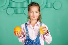 Το κορίτσι παιδιών πίνει το χυμό από πορτοκάλι για το πρόγευμα η έννοια ενός hea Στοκ εικόνες με δικαίωμα ελεύθερης χρήσης