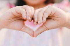 Το κορίτσι παιδιών παραδίδει την καρδιά στοκ εικόνες