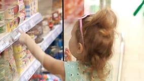 Το κορίτσι παιδιών στο κατάστημα ανοίγει την πόρτα ψυγείων και αγοράζει τις παιδικές τροφές χαριτωμένος ευτυχής χαρακτήρα λίγη υπ απόθεμα βίντεο
