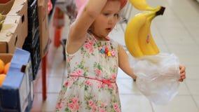 Το κορίτσι παιδιών στο κατάστημα επιλέγει τα φρούτα Υπεραγορά παντοπωλείων και καροτσάκι αγορών απόθεμα βίντεο