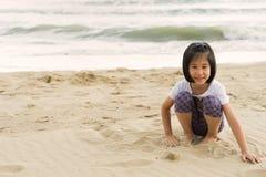 Το κορίτσι παιδιών 6s απολαμβάνει τη θάλασσα παραλιών παιχνιδιού Στοκ Φωτογραφία