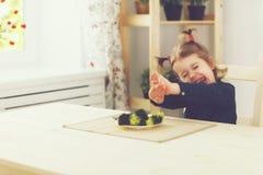 Το κορίτσι παιδιών δεν επιθυμεί και δεν θέλει για να φάει τα λαχανικά στοκ φωτογραφίες με δικαίωμα ελεύθερης χρήσης