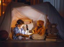 Το κορίτσι παιδιών με ένα βιβλίο και ένας φακός και teddy αντέχουν πριν από πηγαίνουν Στοκ εικόνες με δικαίωμα ελεύθερης χρήσης
