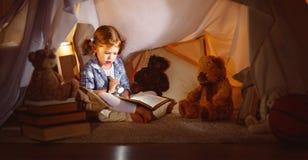 Το κορίτσι παιδιών με ένα βιβλίο και ένας φακός και teddy αντέχουν πριν από πηγαίνουν Στοκ Εικόνες