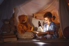 Το κορίτσι παιδιών με ένα βιβλίο και ένας φακός και teddy αντέχουν πριν από πηγαίνουν Στοκ εικόνα με δικαίωμα ελεύθερης χρήσης
