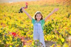 Το κορίτσι παιδιών στον ευτυχή τομέα αμπελώνων φθινοπώρου ανοικτό οπλίζει το κουλούρι κόκκινων σταφυλιών Στοκ Εικόνα