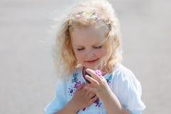 Το κορίτσι παιδιών στράβισε και εξετάζει το χαλίκι στοκ φωτογραφία