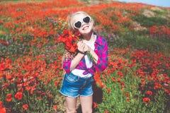 Το κορίτσι παιδιών φορά τον τομέα γυαλιών ηλίου και περιστασιακών ενδυμάτων την άνοιξη με την ανθοδέσμη των παπαρουνών Στοκ Φωτογραφίες