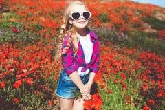 Το κορίτσι παιδιών φορά τον τομέα γυαλιών ηλίου και περιστασιακών ενδυμάτων την άνοιξη με τις παπαρούνες Στοκ Εικόνες