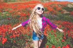 Το κορίτσι παιδιών φορά τον τομέα γυαλιών ηλίου και περιστασιακών ενδυμάτων την άνοιξη με την ανθοδέσμη των παπαρουνών Στοκ Εικόνα