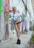Το κορίτσι-πανκ που στέκεται κοντά στον τοίχο με τα γκράφιτι Στοκ Εικόνες