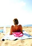 το κορίτσι παραλιών κάνει ηλιοθεραπεία στοκ φωτογραφία με δικαίωμα ελεύθερης χρήσης