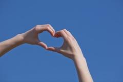 Το κορίτσι παραδίδει τη μορφή καρδιών Στοκ Εικόνα