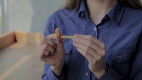 Το κορίτσι παρεμβάλλει ένα κομμάτι των τηγανισμένων πατατών στο δαχτυλίδι κρεμμυδιών φιλμ μικρού μήκους