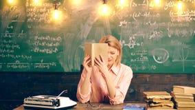 Το κορίτσι παρουσιάζει διαφορετικές συγκινήσεις που καλύπτουν το μισό από το πρόσωπο από τη συνεδρίαση βιβλίων στον πίνακα στη σχ απόθεμα βίντεο