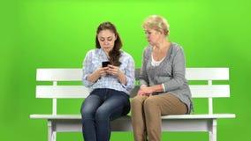 Το κορίτσι παρουσιάζει κάτι στο τηλέφωνο στη μητέρα της πράσινη οθόνη απόθεμα βίντεο
