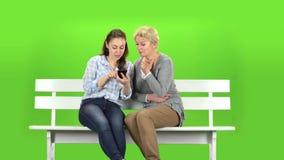 Το κορίτσι παρουσιάζει κάτι στο τηλέφωνο στη μητέρα της πράσινη οθόνη φιλμ μικρού μήκους