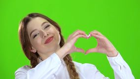 Το κορίτσι παρουσιάζει μορφή καρδιών και χαμογελά πράσινη οθόνη απόθεμα βίντεο