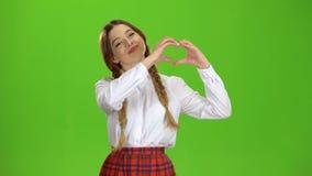 Το κορίτσι παρουσιάζει μορφή καρδιών πράσινη οθόνη φιλμ μικρού μήκους