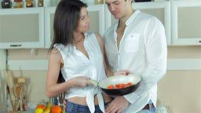Το κορίτσι παρουσιάζει ντομάτες φίλων της σε ένα τηγανίζοντας τηγάνι απόθεμα βίντεο