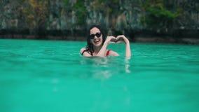 Το κορίτσι παρουσιάζει σημάδι καρδιών στο νερό φιλμ μικρού μήκους