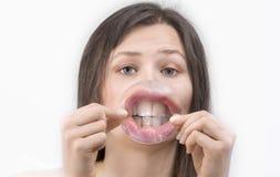 Το κορίτσι παρουσιάζει τα χείλια και δόντια της μέσω του μεγάλου loupe Στοκ Εικόνες