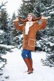 Το κορίτσι παρουσιάζει τρίχα στο χειμερινό πάρκο στην ημέρα Δέντρα του FIR με το χιόνι Redhead πλήρες μήκος γυναικών Στοκ Εικόνες