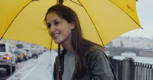 Το κορίτσι περιμένει το λεωφορείο της κάτω από μια ομπρέλα απόθεμα βίντεο