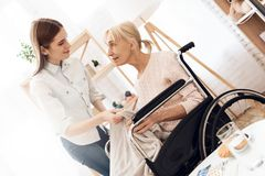 Το κορίτσι περιποιείται την ηλικιωμένη γυναίκα στο σπίτι Το κορίτσι καλύπτει τη γυναίκα με το θερμό κάλυμμα στοκ εικόνες
