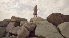 Το κορίτσι περπατά πάνω από το βουνό, που ισορροπεί σε έναν στενό λόφο, κρατώντας ένα κινητό τηλέφωνο στο χέρι της σε αργή κίνηση απόθεμα βίντεο