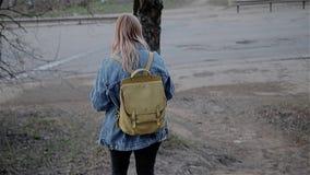 Το κορίτσι πηγαίνει κάτω από έναν μικρό λόφο στο πάρκο πόλεων Οι βλαστοί καμερών από πίσω σε σε αργή κίνηση φιλμ μικρού μήκους